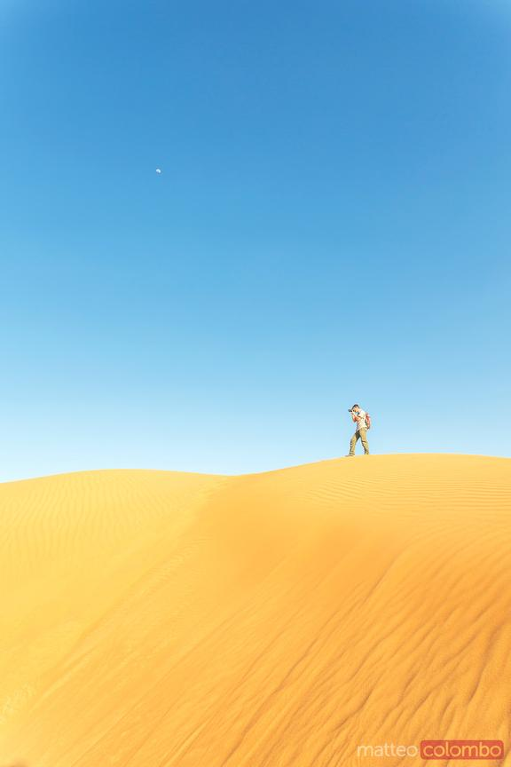 Oman, Wahiba Sands. Tourist taking a photo from the sand dunes