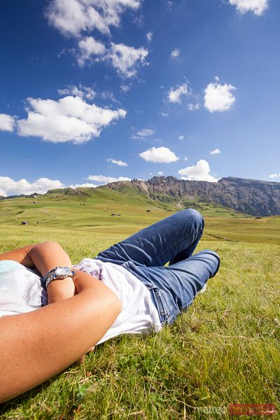 Adult woman relaxing on meadow in the mountains