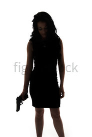 A Figurestock image of a woman holding a gun, in silhouette, standing, looking down – Shot from mid level.