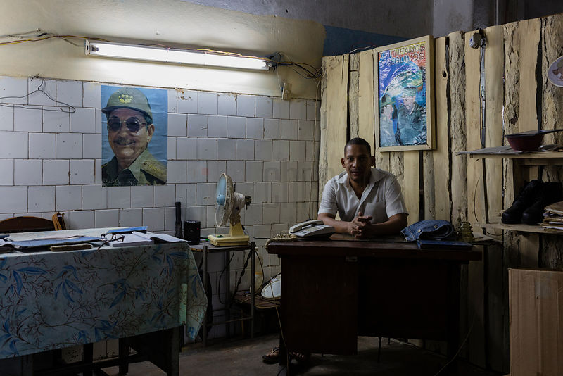 Market Manager with a Portrait of Raú Castro in the Background
