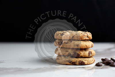 Stacked chocolate chip cookies on a white marble table