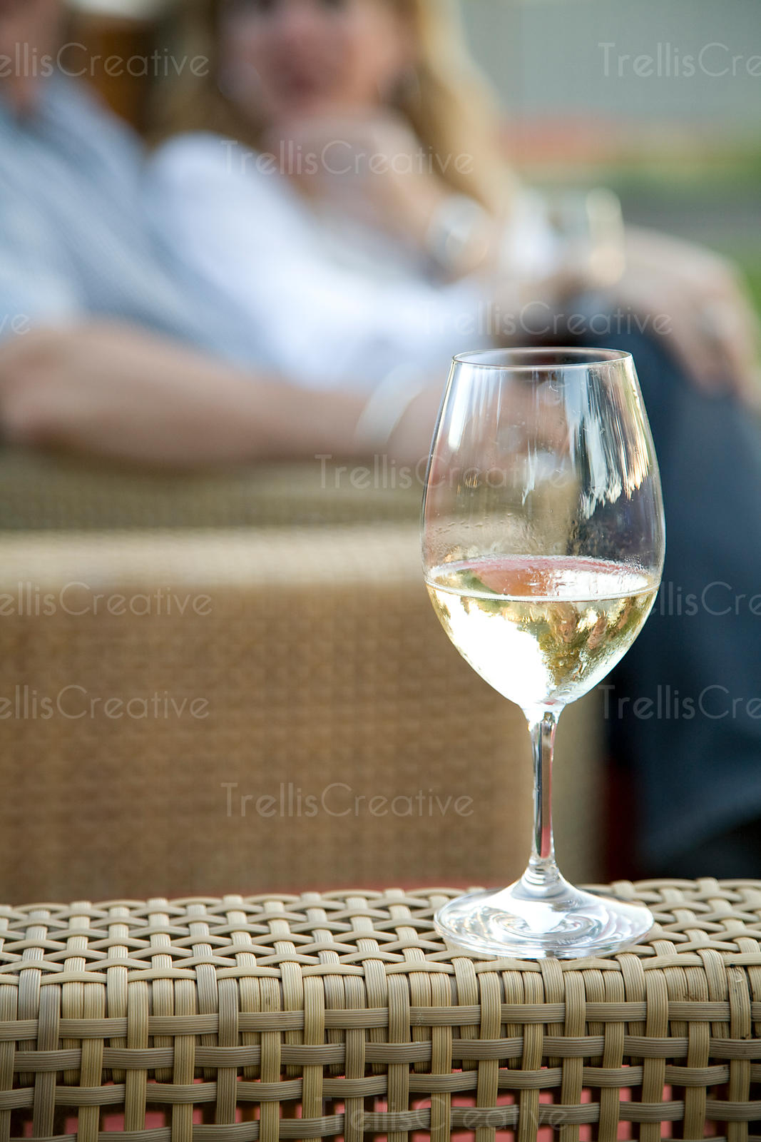 glass of white wine on rattan chair with couple in background