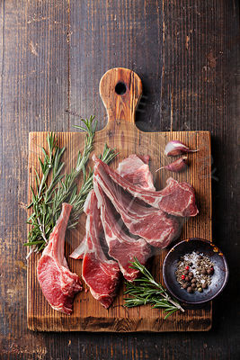 Raw fresh Lamb Meat ribs and seasonings on dark wooden background