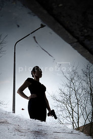 An atmospheric image of a mystery woman, holding a gun in the street, reflected in a puddle.