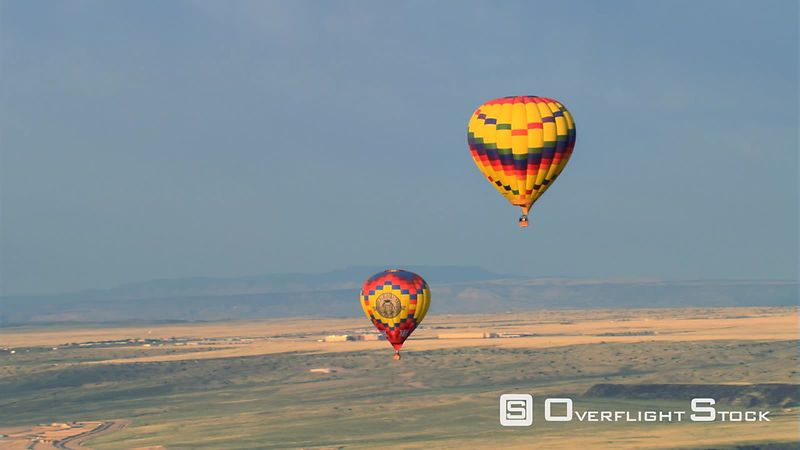 Mid-air view of two hot air balloons gliding over Albuquerque.