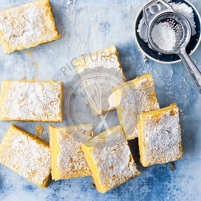 Pieces of homemade lemon slice with icing sugar in a sifter.