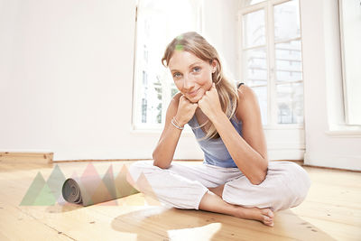 Yoga woman sitting on floor of a yoga studio