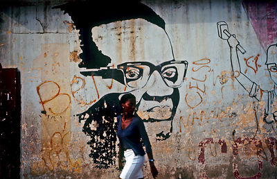 Angola - Luanda - A woman walks in front of a poster of Agostinho Neto