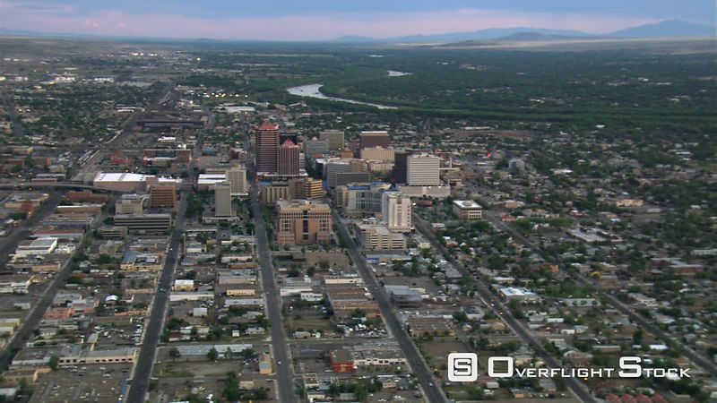 Wide flight past downtown Albuquerque with Rio Grande beyond cityscape.