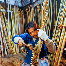 Chibata Kanjuro, whose family has been making bows since the 15th century, bends the bamboo frame of a new bow in his worksho...