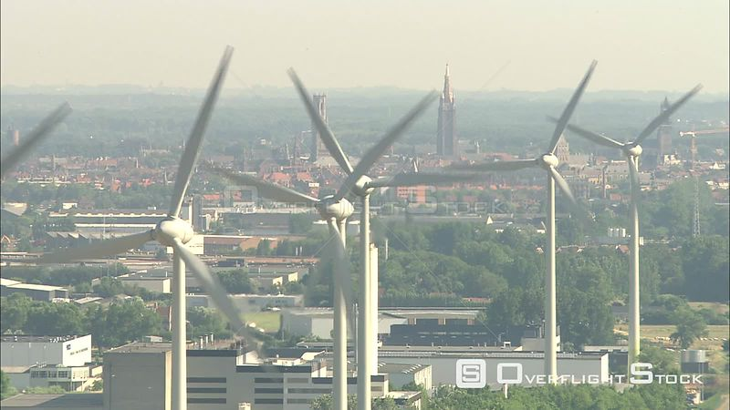 Looking through wind turbines to spires of Bruges, Belgium