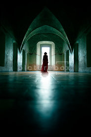 An atmospheric image of the silhouette of a woman, looking out of a window, in an old room.