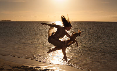 Silhouette of a Bodyart Dance Company dancer jumping in the surf at sunset, in Turks & Caicos