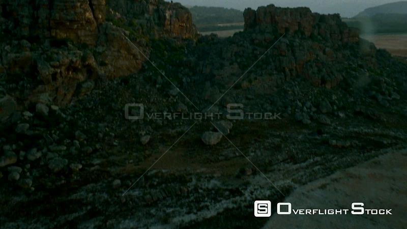 Aerial shot rocky terraced mountain terrain with sparse vegetation and through gap into valley below Botswana