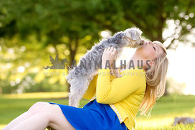 small dog on top of woman kissing her