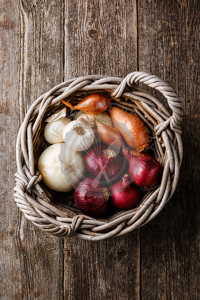 Different types of onions in basket on wooden background