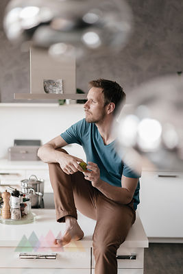 Pensive man sitting on kitchen counter looking at distance