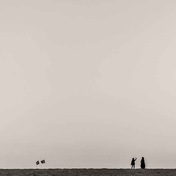 Qatar. Two girls on the sand dune, connecting.