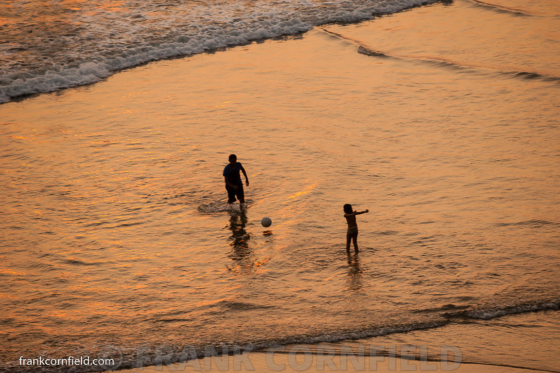 Man and young girl in surf at Varkala beach.