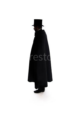 A Victorian man, standing in a hat and cloak, in silhouette – shot from eye level.