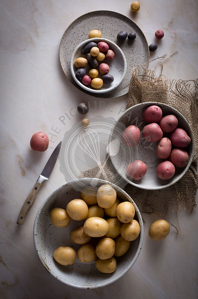 Different kinds of mini potatoes in a ceramic bowl on a marble table on top view