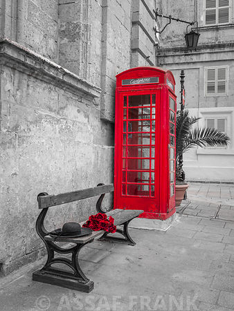 Bunch of roses and hat on bench by a telephone booth in Mdina, Malta