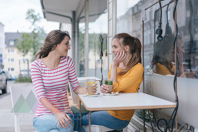 Two girlfriends meeting in a coffee shop, talking