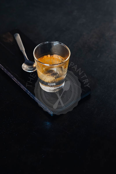 Empty glass of espresso on stone table