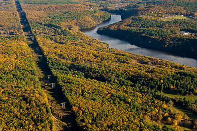 Aerial view of power lines cutting a swath through forest next to the Connecticut River in Gill, Massachusetts, USA, November...