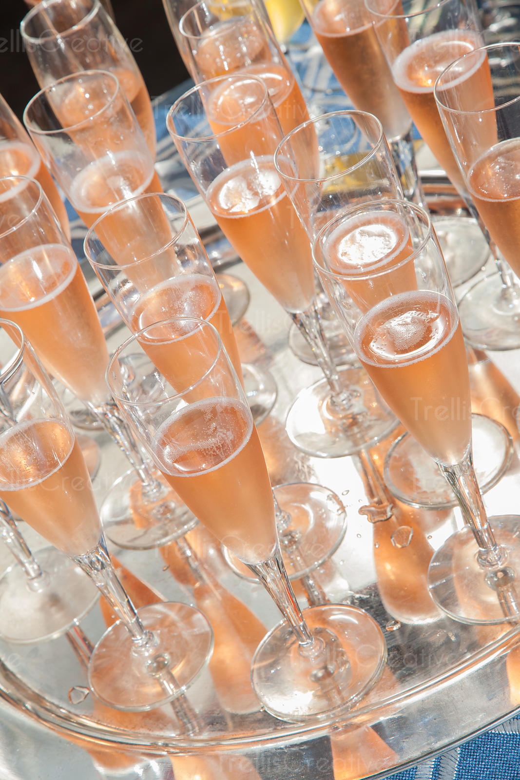 A silver tray with glasses of rose sparkling wine