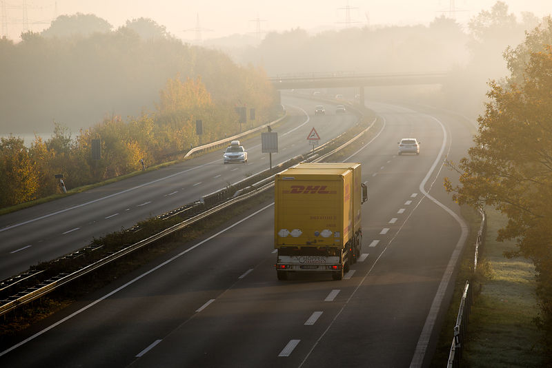 DHL Parcel delivery truck travelling on the Autobahn through the German countryside on a misty day