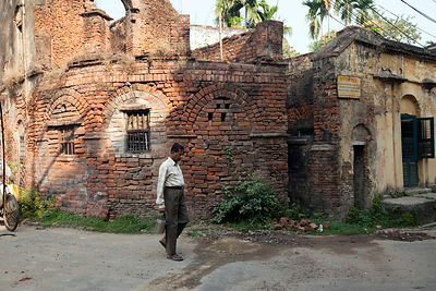 India - Chandannagar - A man walks past a derelict French colonial house
