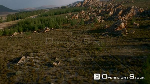 Aerial medium shot up mountain side with rocky outcrops surrounded by vegetation towards valley below Botswana