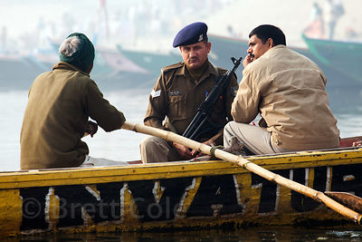 A military or policeman with his gun on a boat on the Ganges River, Varanasi, India.