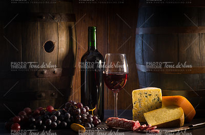 Glass of red wine cheeses grapesand barrel on brown wood
