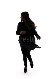 A mystery woman, in silhouette, running away from something and looking over her shoulder – shot from eye level.