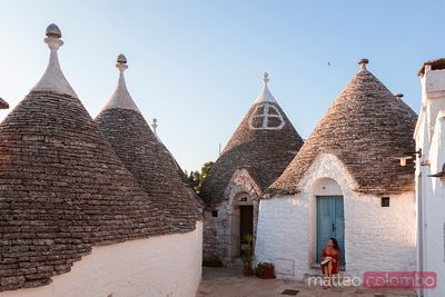 Woman visiting the Trulli area, Alberobello, Apulia, Italy