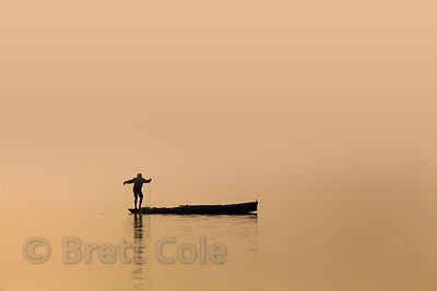 A fisherman pulls in a net on the Ganges River at sunrise, Varanasi, India.