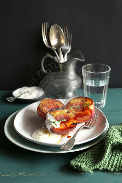 Plate with grilled peach with greek yogurt and honey and decorated with fresh thyme