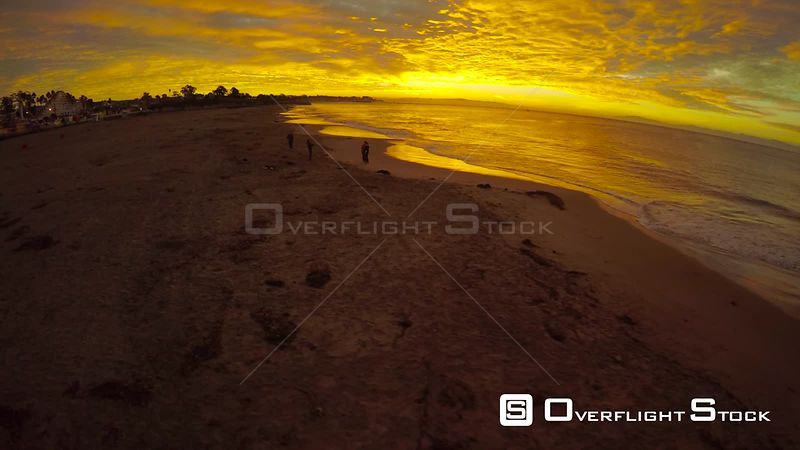 People play at shore of ocean sunrise