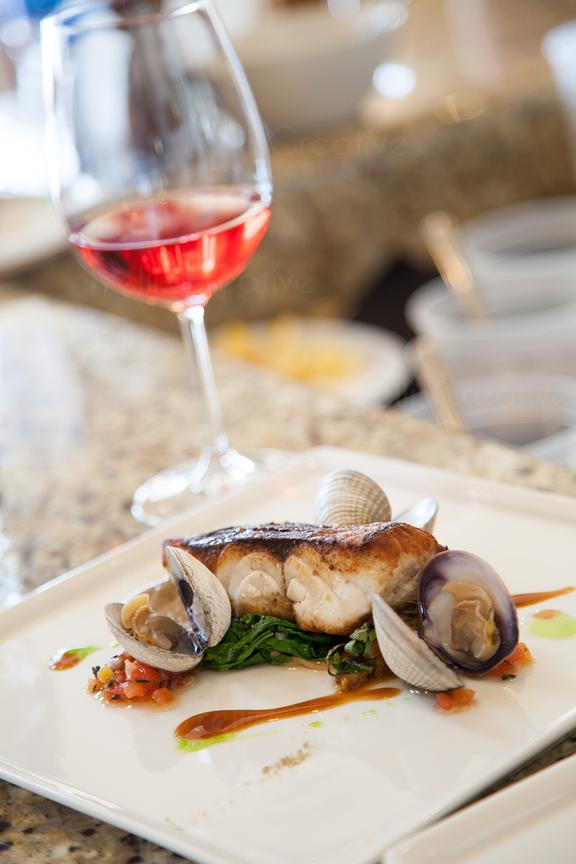 Pan seared white fish served with Manilla clams and a glass of rose wine