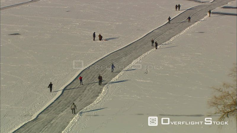Over ice skaters on a meandering path through a snowy rural landscape