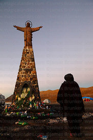 Woman praying at base of Christ statue at dawn, La Cumbre, Cordillera Real, Bolivia