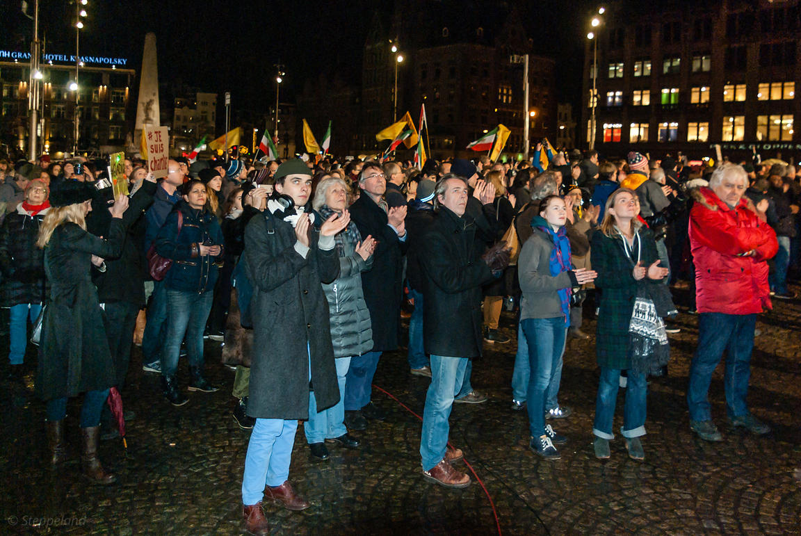 Amsterdam, Netherlands 2015-01-08: People applaud after the minute of silence, while following the projections on the screen above them.