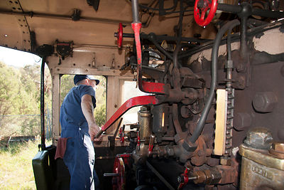 train driver operating the controls of a steam engine