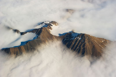 Aerial photo of mountain peaks and cirques through cloud layer. Spitsbergen, Svalbard, July.