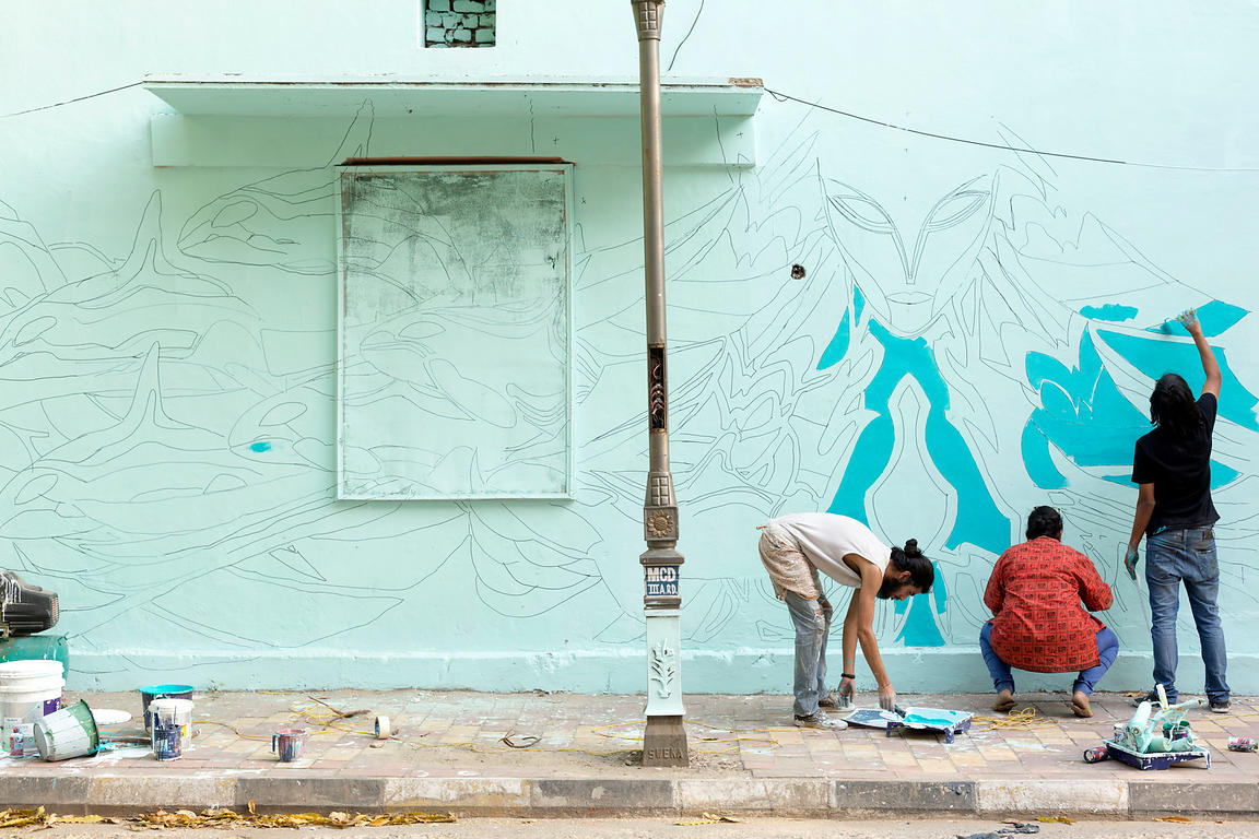 Artist Tanmay working on his first design on a wall in the Lodhi Colony area of New Delhi