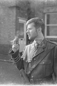 A reproduction of an old photograph of a first world war British officer smoking a cigarette.