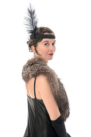 A vintage 1920s - 1930s woman in a long black dress with a headband and feather – shot from eye level.