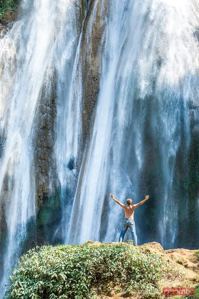 Adult man with arm raised in front of waterfall